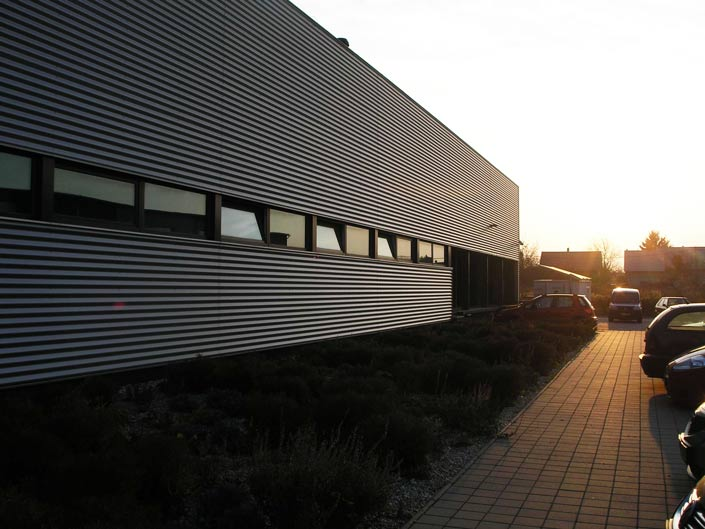 Стальной сайдинг широко применяется при облицовке фасадов коммерческих и промышленных зданий